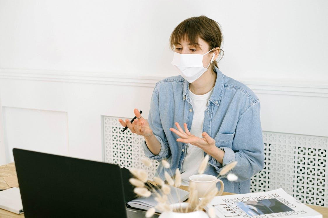 Woman in Face Mask Having Video Call