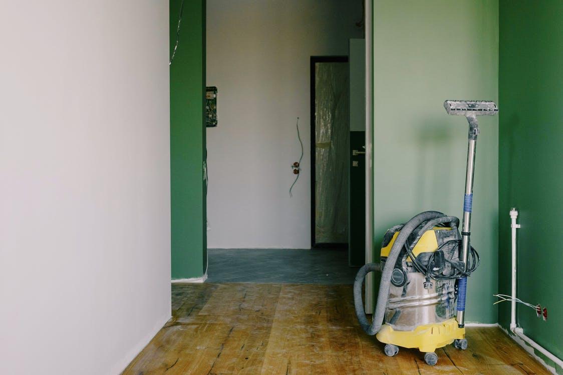Gray Vacuum Cleaner on Brown Wooden Parquet Floor